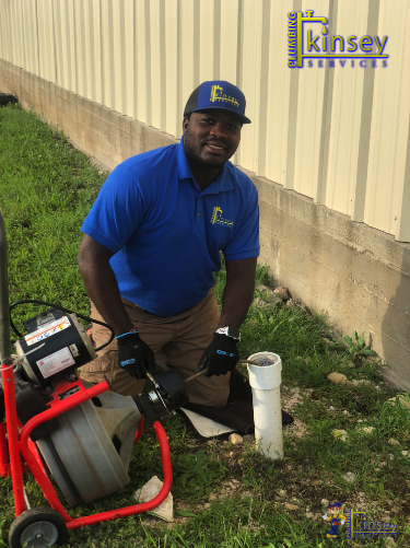 Kinsey Plumbing Expert on-site cleaning a drain.