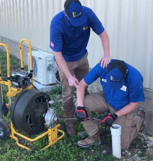 Kinsey plumbers snaking a drain.